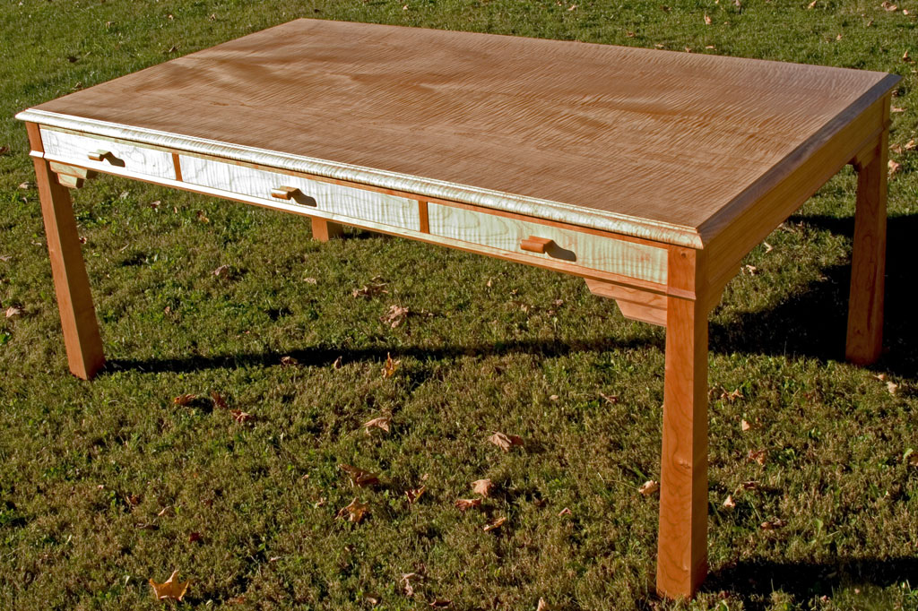 This curly maple and cherry map table features drawers and bracketed legs.